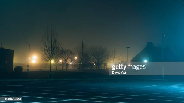 an empty car park with street lights glowing in the distance on a mysterious moody,  foggy atmospheric winters night - parking stock pictures, royalty-free photos & images