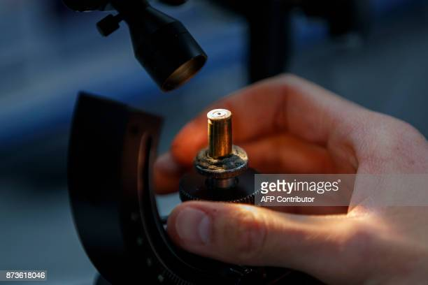 An empty cartridge is seen whilst forensic officer matches firing details and references cartridge cases with a ballistic microscope at the London...