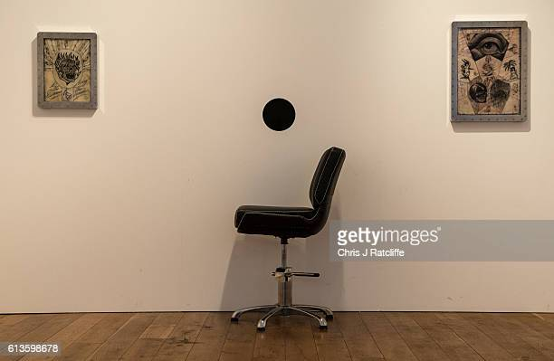 An empty chair and hole in the wall awaits a recipient of a free tattoo at event 'Whole Glory' on October 9 2016 in London England The recipient sits...