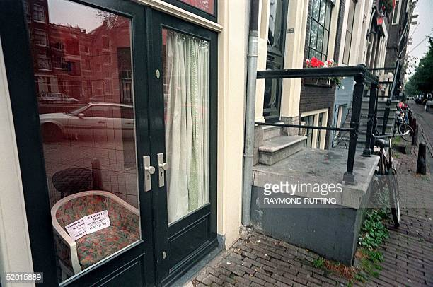 An empty chair behind a glass door carries a Room To Let sign in an Amsterdam street 03 September as a result of a decision by the local mayor that...
