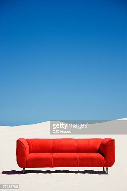 An empty couch alone in the middle of the desert