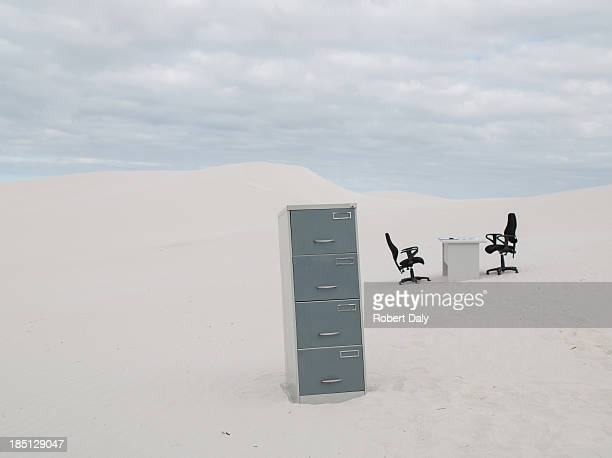 An empty desk and chair with filing cabinet in the middle of desert