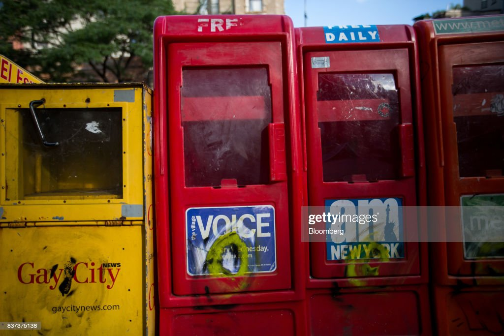 An empty distribution box for The Village Voice, second left, is seen in the East Village neighborhood of New York, U.S., on Tuesday, Aug. 22, 2017. Peter Barbey, owner of The Village Voice since 2015, has decided to no longer produce a print edition of the alt-weekly publication. The company's announcement, made Tuesday afternoon, came as a surprise, a shock and a disappointment to the larger media industry on Twitter. Photographer: Michael Nagle/Bloomberg via Getty Images