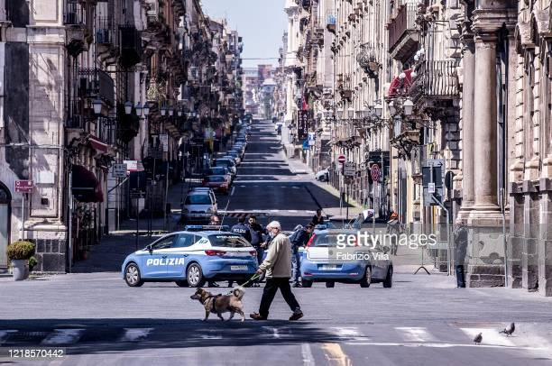 An empty downtown street police patrols and a gentleman with his dog on Easter Monday during the Covid19 emergency on April 13 2020 in Catania Italy...