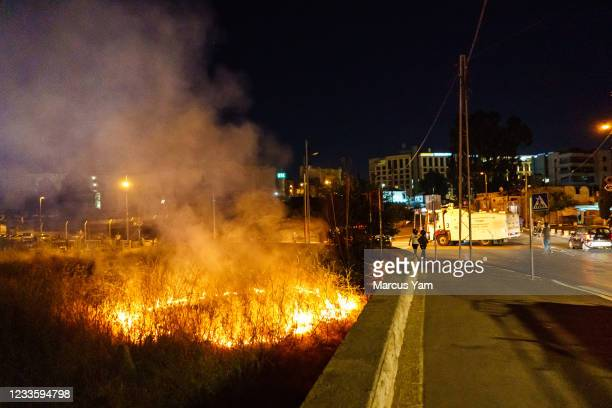 An empty field is set on fire outside the Sheikh Jarrah neighborhood in Jerusalem, Israel, Monday, June 21, 2021. Palestinians and their supporters...
