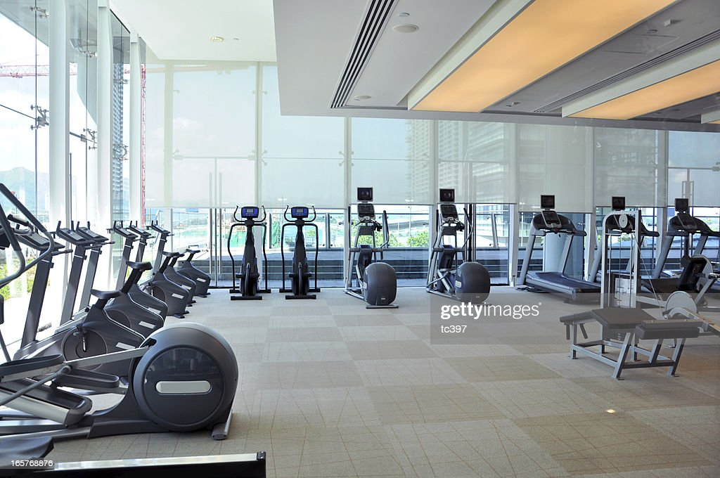 An empty gym room with rows of running machines stock