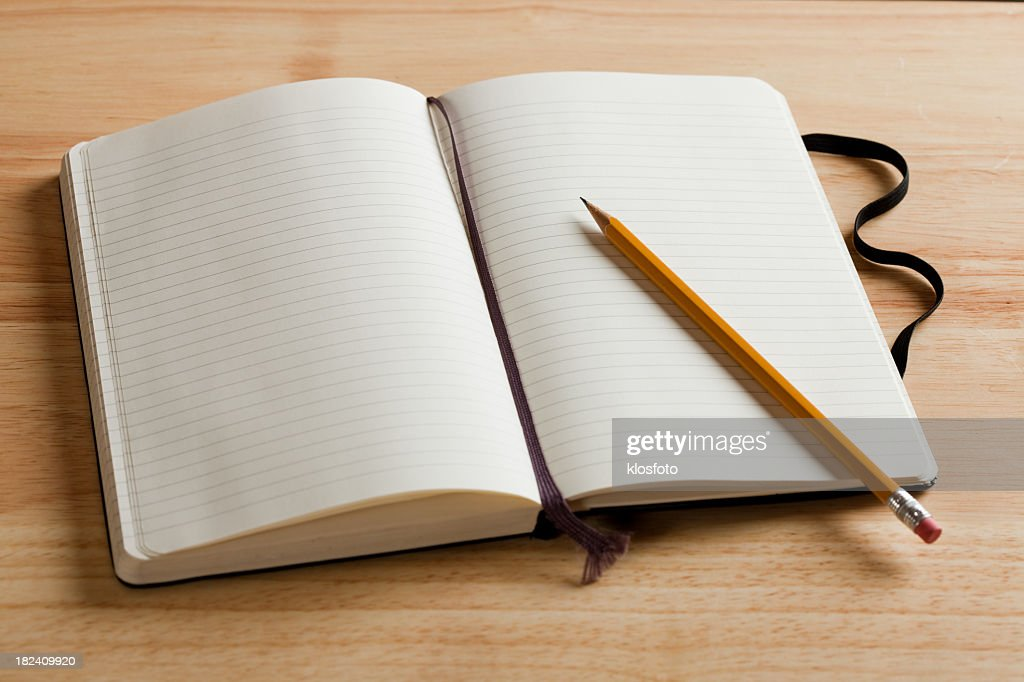 An empty journal open on a desk with a pencil : Stock Photo