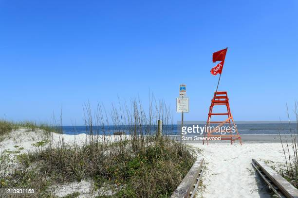 An empty lifeguard chair with a No Swimming flag is seen at Jacksonville Beach amid the coronavirus outbreak on March 21 2020 in Jacksonville Beach...