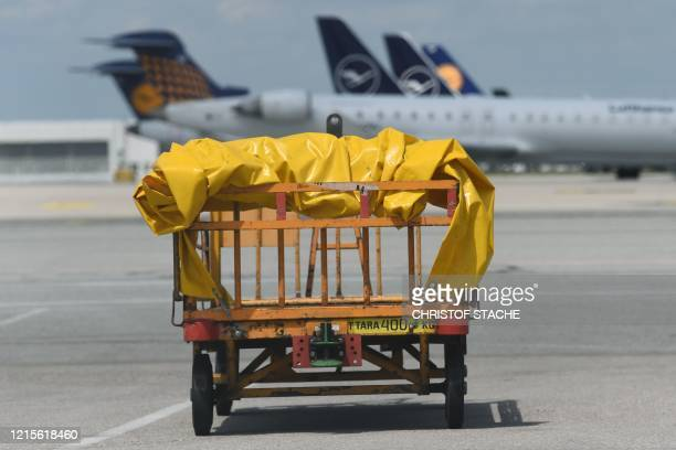 "An empty luggage cart stands in front of planes of the German airline Lufthansa which are parked at the ""Franz-Josef-Strauss"" airport in Munich,..."