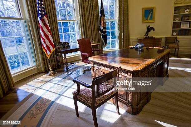 An empty Oval Office at the White House in Washington with family photos of President Barack Obama behind his desk