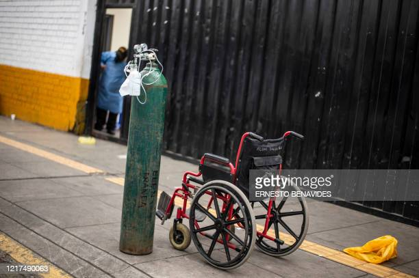 An empty oxygen cylinder and a wheelchair are seen at the entrance for patients with respiratory diseases of the 2 de Mayo Hospital in Lima on June 3...