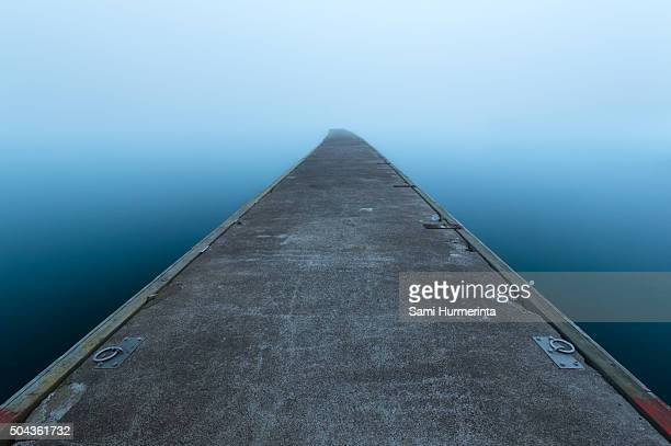An empty pier on a foggy morning