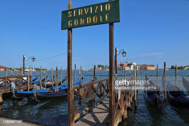 an empty pier with stationary gondolas during covid-19 pandemic - gondola traditional boat stock pictures, royalty-free photos & images