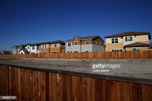 An empty plot of land sits in front of a row of new homes at a housing development on December 4 2013 in Dublin California According to a Commerce...