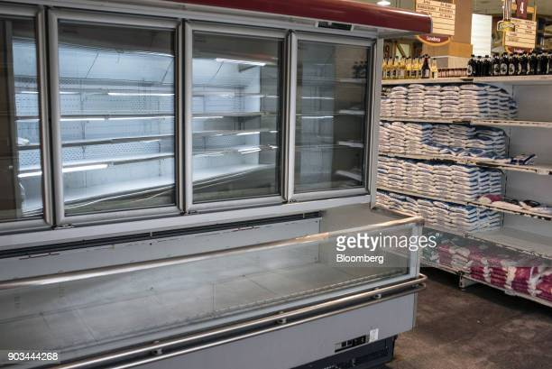 An empty refrigerator unit stands at a grocery store in Caracas Venezuela on Tuesday Jan 9 2018 Hordes of desperate shoppers emptied supermarkets and...