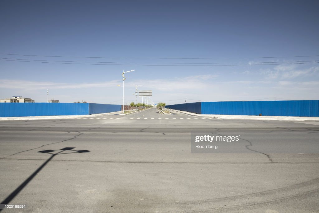 An empty road runs past hoardings around two construction sites in Golmud, Qinghai province, China, on Wednesday, July 25, 2018. Amid rising fears about a trade war, China's policy makers have unveiled measures to boost infrastructure construction and credit to smaller firms, as well as tax cuts. Photographer: Qilai Shen/Bloomberg via Getty Images