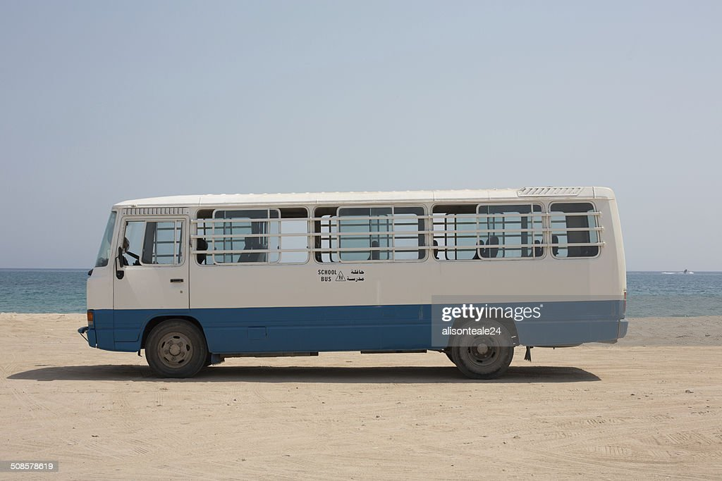 An empty school bus parked on the sand, Dibba, Oman : Stock Photo