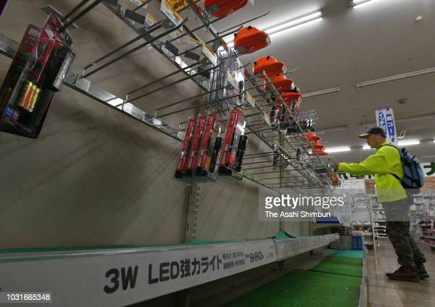 An empty shelf is seen as flashlights and power generators are almost sold out at a shop on September 11 2018 in Sapporo Hokkaido Japan A male...