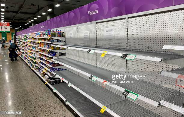 An empty shelf usually stocked with tissue is seen at a supermarket in Melbourne on March 5, 2020. - COVID-19 coronavirus fears have triggered runs...