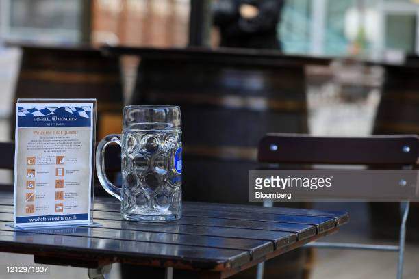 An empty stein glass sits beside a social distancing and hygiene information sign outside a Bavarian-themed beer hall ahead of reopening in Berlin,...