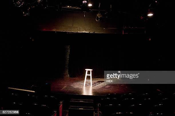 An empty stool spot lit on a stage
