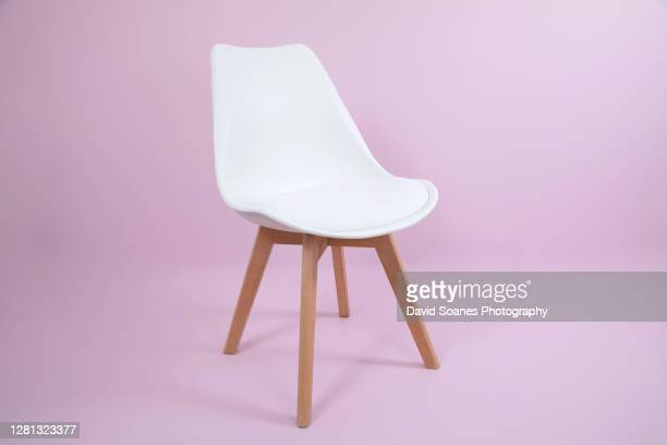 an empty white chair against a pink background - david soanes stock pictures, royalty-free photos & images