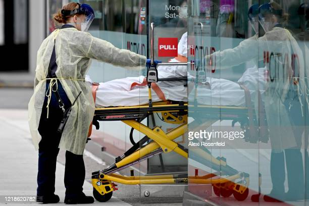 An EMS worker wheels a COVID19 patient out of a CityMD amid the coronavirus pandemic on April 12 2020 in New York City United States amid the...