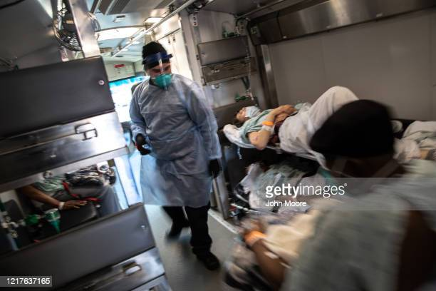 An EMT wearing personal protective equipment , prepares to unload COVID-19 transfer patients at the Montefiore Medical Center Wakefield Campus on...
