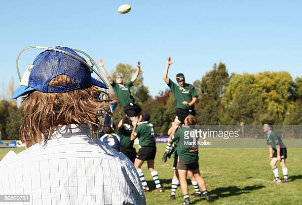 An Emus supporter wearing a novelty hat as part of Mad Hat Day watches the action during the first grade Country Rugby Union match between the Orange...
