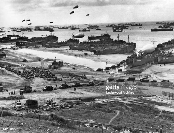 An endless stream of supplies flow from the transports and landing craft at Normandy headed for the front in France while barrage balloons protect...