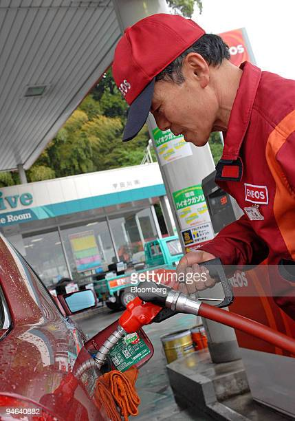 An Eneos gas station employee fills a customer's tank in Tokyo Japan Friday May 19 2006