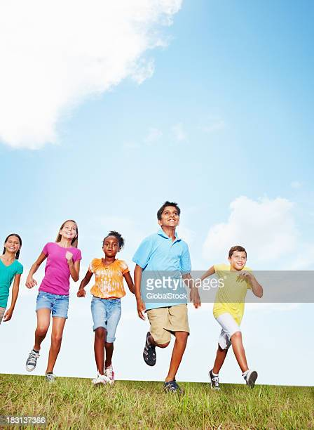 An energetic friends running on grass against sky - copyspace