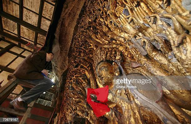 An engineer checks on the Onethousandhand Goddess of Mercy sculpture at the Dazu Stone Carving Site on November 30 2006 in Dazu County of Chongqing...