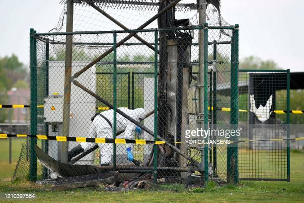 An engineer checks the base of a 5G mast erected by telecom operator 'Proximus' that was set on fire in Peltheide Limburg province on the eve of...
