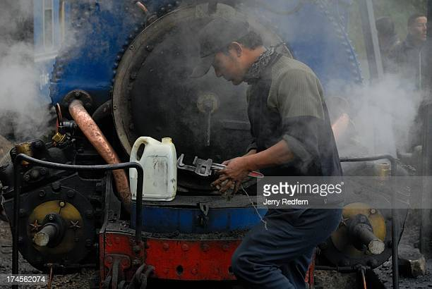 An engineer fills pistons with oil on one of the historic coalfired steam engines that pulls the Toy Train between Ghoom and Darjeeling as it is...