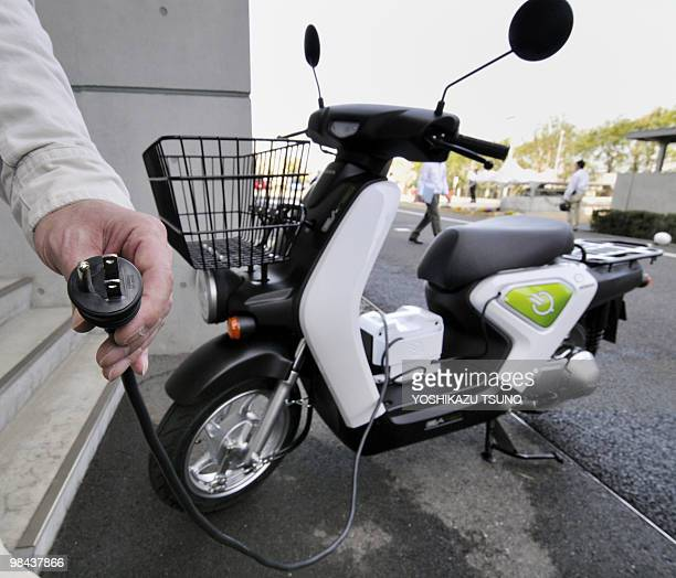 An engineer for Japan's Honda Motor demonstrations how to charge the company's prototype model of a new electric motorcycle called the 'EVneo' at the...