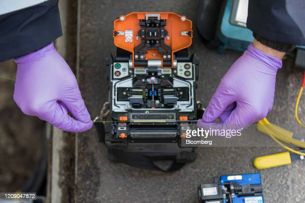 An engineer for Openreach Ltd attaches fibre optics to a control unit in Chelmsford UK on Tuesday March 31 2020 The UK could tighten its lockdown...