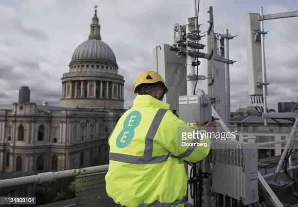 An engineer from EE the wireless network provider owned by BT Group Plc checks 5G equipment undergoing trials overlooking St Paul's Cathedral in the...