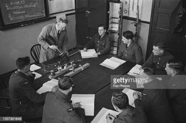 An engineer holding a bomb as he instructs officers sat around a table in a classroom at the RAF Training School at RAF Manby near the village of...