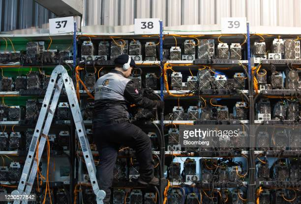 An engineer inspects cabling from racks of application-specific integrated circuit mining devices and power units at the BitCluster cryptocurrency...