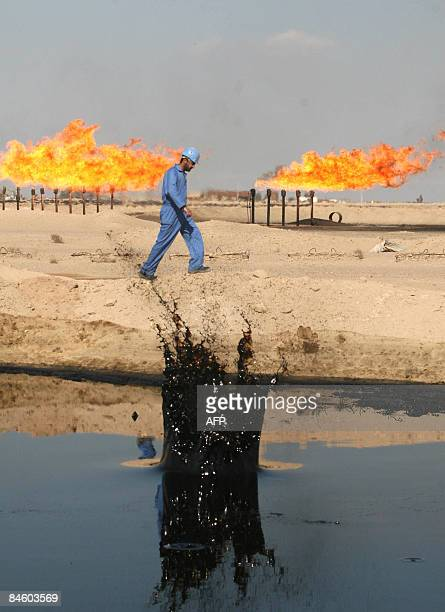 MORGAN An engineer makes his way past an oil pond at the Barjisiya oil fields in Zubair One south west of the city of Basra 550 kms from Baghdad on...