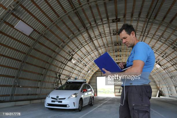 An engineer monitors information from a driverless Toyota Motor Corp Prius hybrid car operated by YandexTaxi part of YandexNV during a selfdriving...