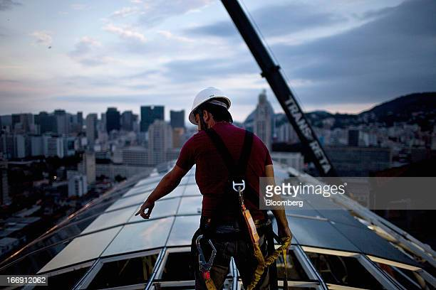 An engineer oversees workers installing glass on the rooftop of a cable car station in Rio de Janeiro, Brazil, on Tuesday, April 16, 2013. Scheduled...