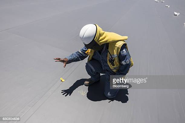 An engineer performs a location test on the geomembrane liner on top of a new industrial pool inside the Salar de Uyuni in Potosi Bolivia on Saturday...