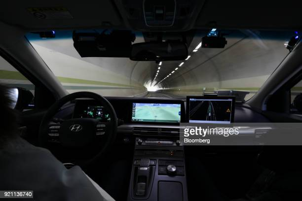 An engineer rides in the driver's seat of a Hyundai Motor Co Nexo autonomous fuel cell electric vehicle during a test drive in Pyeongchang Gangwon...