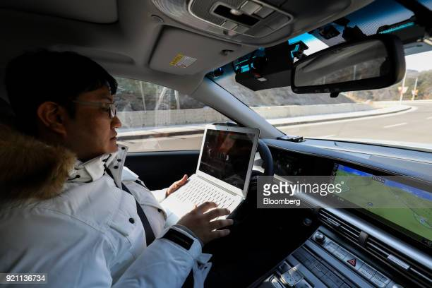 An engineer uses a laptop computer while riding in the driver's seat of a Hyundai Motor Co Nexo autonomous fuel cell electric vehicle during a test...