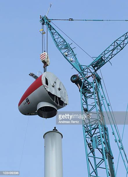 An engineer waits for a part of a turbine carried by a huge crane next to a row of wind turbine masts under construction on August 20, 2010 near...