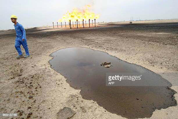 An engineer walks across the Zubair oil field in southern Iraq on January 21 2010 Zubair produces around 227000 barrels of oil per day according to...