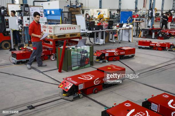 An engineer watches an 'Easybot' mobile robot also known as an AGV or automated guided vehicle following a taped line during testing inside the...