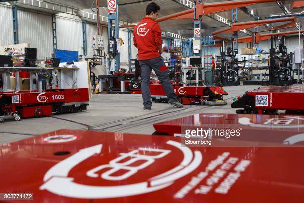 An engineer watches an 'Easybot' mobile robot also known as an AGV or automated guided vehicle follow a taped line during testing inside the...